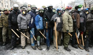 Pro-European protesters stand in line holding wooden sticks.