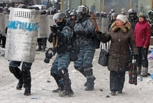 A woman holds a wooden cross as riot police aim their weapons