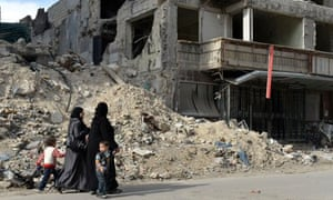Syrian women and children walk past ruins in Aleppo, April 2013