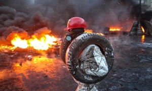 A pro-European integration protester carries tyres at the site of clashes with riot police in Kiev.