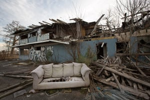 Rebuilding New Orleans: A discarded couch in front of an abandoned partially burnt-down building