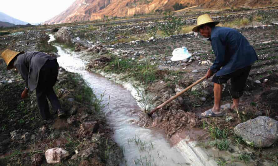 Farmers dig ditches to lead water from a white polluted stream into farm fields, in Dongchuan district of Kunming, Yunnan province