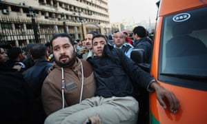 A man carries an Egyptian police officer to an ambulance after the car bombing in central Cairo