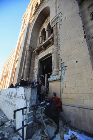 Police officers and people gather in front of the damaged Museum of Islamic Art building near the Egyptian police headquarters