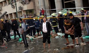 A police officer stands in from of the Egyptian police headquarters following a blast in Cairo.