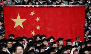 Graduates sit next to a Chinese flag during a graduation ceremony