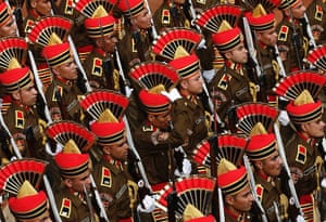 A policeman (C) adjusts his headgear as he marches with others during the full dress rehearsal for the Republic Day parade in New Delhi.