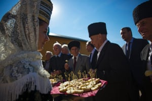 A woman in traditional dress welcomes a delegation of diaspora Circassians with a traditional bread and salt dish as they visit a school in Bolshoy Kichmay, Greater Sochi.