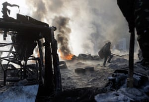 Protests in Ukraine: A protester walks near burning tyres after the clashes with police in Kiev