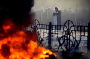 Protests in Ukraine: A priest prays in front of the riot police in Kiev