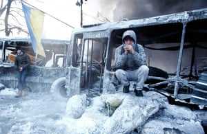 Protests in Ukraine: An anti-government protester sits near a burnt out vehicle in Kiev