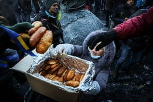 Ukraine: A woman in Kiev hads out bread rolls to protestors