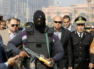 Cairo protest: A policeman guards Cairo's state security chief, Osama al-Saghi