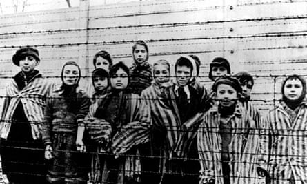 A group of children in striped concentration camp uniforms behind barbed wire fencing at Auschwitz