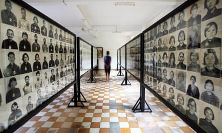 A tourist walks past portraits of Khmer Rouge victims at the Tuol Sleng Genocide Museum, Phnom Penh