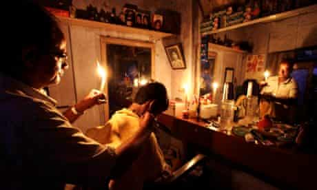 A barber in Kolkata gives a customer a haircut during the Indian blackout of 2012