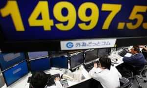 Employees of a foreign exchange trading company work under a monitor displaying the Nikkei share average in Tokyo January 27, 2014.