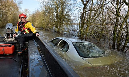 A policeman on a boat looks at a car submerged in floodwater