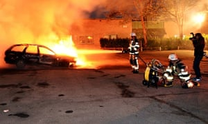 A car burning after riots in Stockholm in 2013.