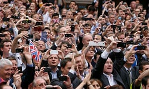 Spectators take pictures with their smartphones
