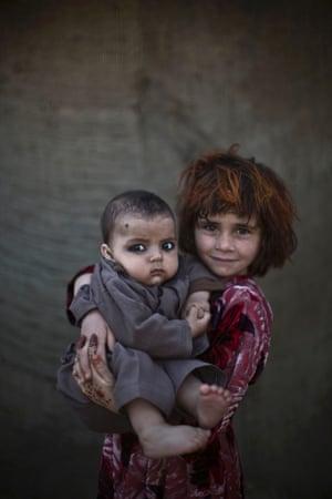 Khalzarin Zirgul, six, holds her cousin, three-month-old Zaman.