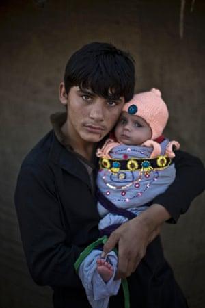 Shahzada Saleem, 15, holds his nephew, two-month-old Satara