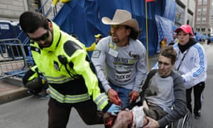 An emergency responder and volunteers, including Carlos Arredondo in the cowboy hat, push Jeff Bauman in a wheelchair after he was injured in an explosion near the finish line of the Boston marathon bombing.