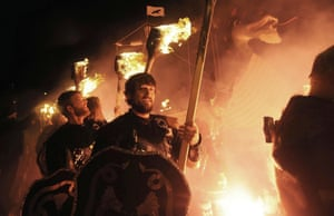 Participants dressed as Vikings carry burning brands.