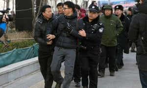 Chinese police manhandle a foreign photographer away from the Beijing court where Xu Zhiyong was sentenced to jail. Two more members of his movement have been convicted for their activism.