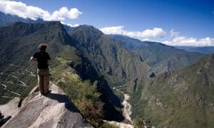 Man standing on top of Wayna Picchu looking down to Machu Picchu, Peru'