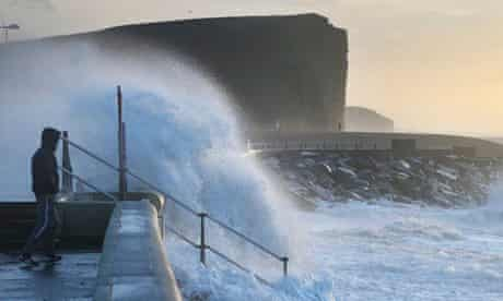 A man looks out from the seafront at West Bay during stormy weather in Dorset