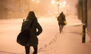 People make their way through snow-covered streets, on foot as traffic came close to a standstill in Brooklyn, New York, USA, 3 January 2014