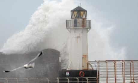 Waves crash over Ardrossan harbour lighthouse in Ardrossan, Scotland.