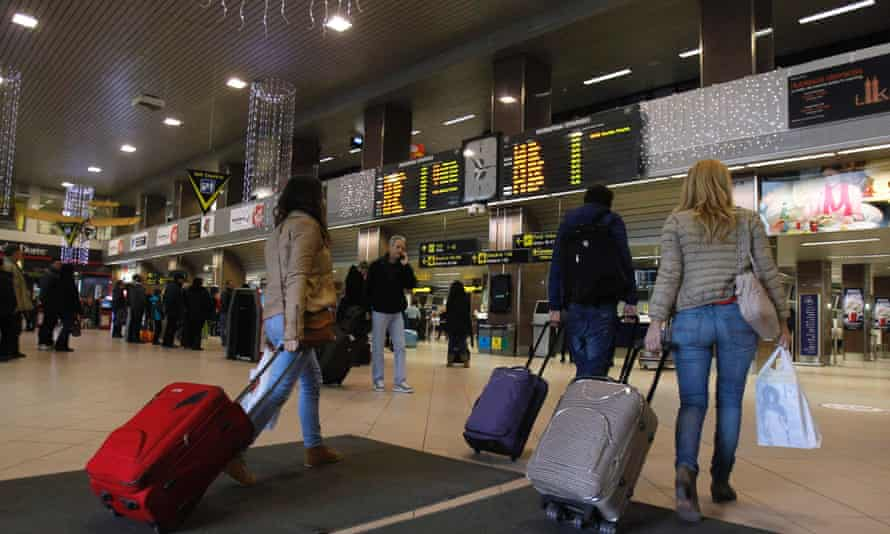 Romanians carry their luggage for a flight to Heathrow airport in Britain, at Otopeni international airport near Bucharest