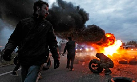 French farmers throw tyres on a fire in protest against the eco tax