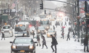 Pedestrians brave wind and snow as they cross Fifth Avenue, Friday, Jan. 3, 2014, in New York