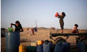 Palestinian children drink water in Younis