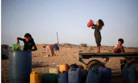 Palestinian children drink water in Younis