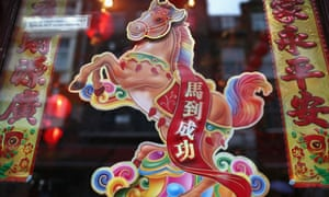An image of a horse hangs in a restaurant window in China Town, London.
