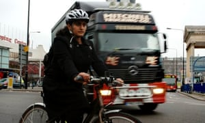 A cyclist negotiates the Elephant and Castle roundabout in London with a lorry behind