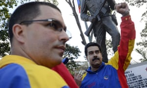 Venezuelan President Nicolas Maduro raises his fist next to vice-president Jorge Arreaza, during a rally.