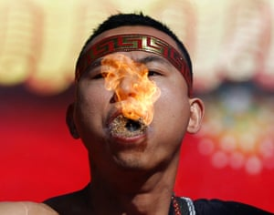 A man spits out a flame as he performs a feat of strength during Chinese New Year celebrations at Ditan Park, Beijing.