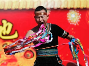 A man pulls ribbons from his mouth as he performs during the opening of the Temple Fair at Ditan Park, in Beijing.