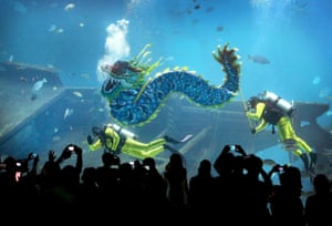 Divers carrying a man-made dragon, wave to the watching crowds at the South East Asia Aquarium at Resorts World Sentosa in Singapore.