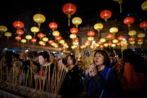 Worshippers burn incense and pray at the Wong Tai Sin Temple in Hong Kong.