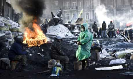 Ukrainian protesters warm up themselves on the barricade during ongoing protests in Kiev, Ukraine. P