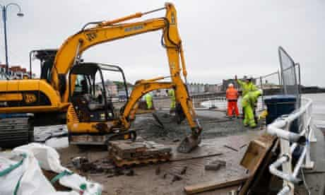 Workers repair the seawall in Aberystwyth in advance of expected flooding on the Welsh coast