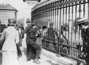 Before the war: A police officer tries to remove a Suffragette from railings