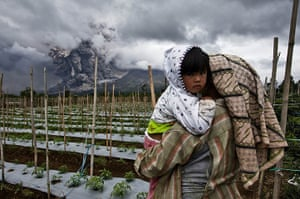 Mount Sinabung: A woman carries her daughter in a nearby field