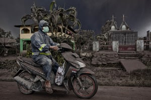 Mount Sinabung: A motorcyclist as drives on a road covered with ash